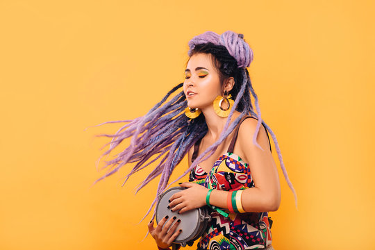 Hipster woman with violet dreadlocks and colored clothes playing on ethical mini drum on yellow background
