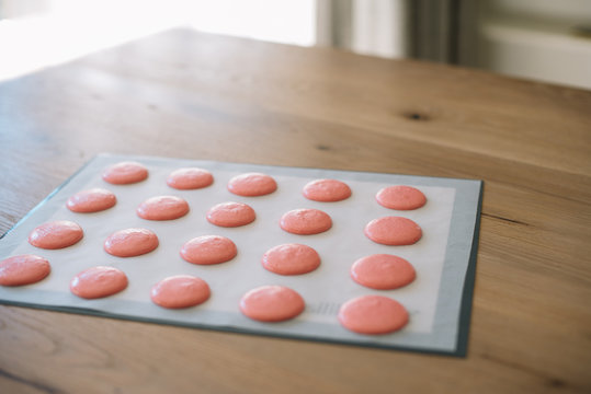 Macaroons ready for baking lie on a silicone baking mat
