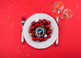 Christmas New year dinner concept color flat lay with dish and festive ornament inside on red monochrome background