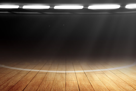 Close up view of a basketball court with wooden floor and spotlights