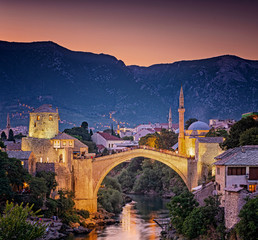 Fotobehang Aubergine Colorful sunset over the medieval bridge of Mostar