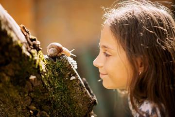 Joyful meeting of a little girl and a snail. Summer photo in the rain.