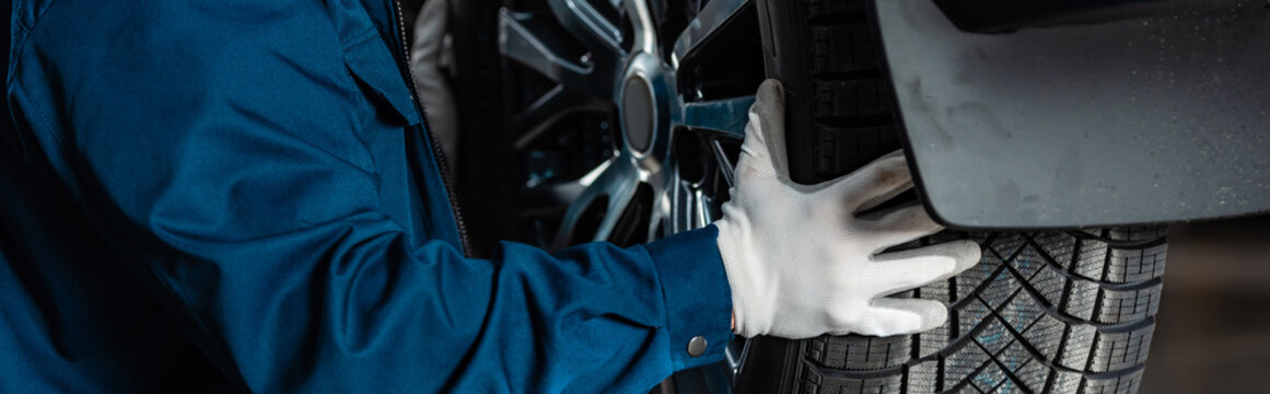 cropped view of mechanic installing wheel on car in workshop, panoramic shot