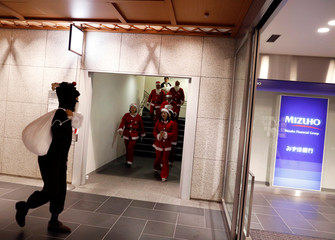 Workers dressed as Santa Clauses and other Christmas characters prepare for a parade around Marunouchi business district to encourage the area promotion, in Tokyo