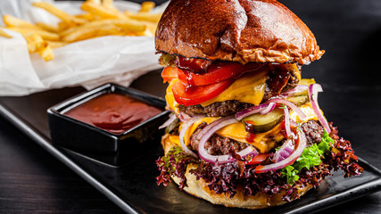 American cuisine. Large royal burger with a double meat cutlet, bacon, tomatoes, cucumbers, cheese, skull, red onions and a sauce. Copy space, background image
