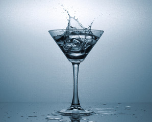 A Martini glass with ice and a spectacular splash of the drink.