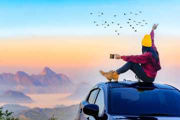 Woman traveller enjoy coffee time on her owns roof of the car with scenery view of the mountain and mist morning in background Fotomurales