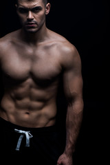 sexy muscular bodybuilder with bare torso isolated on black