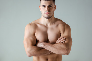 sexy muscular bodybuilder with bare torso posing with crossed arms isolated on grey