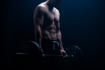 cropped view of muscular bodybuilder with bare torso excising with barbell on black background