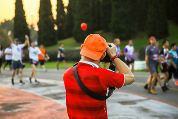 photographer taking a photo  during group people running a marathon