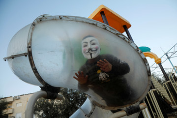 Palestinian boy wearing a mask enjoys a ride in a park in Bethlehem in the Israeli-occupied West Bank