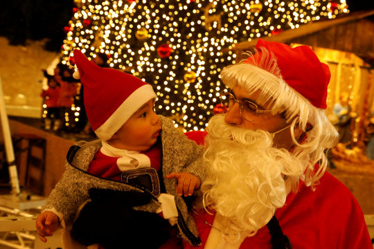 A man dressed as Santa Claus holds a baby at Manger Square in Bethlehem in the Israeli-occupied West Bank
