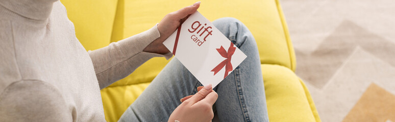Cropped view of young woman holding gift card on sofa, panoramic shot