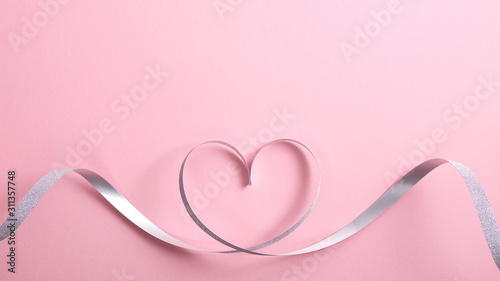 Heart shape border made of silver ribbon on pink background. Greeting card mockup for Valentine's Day or birthday, Mother's day. Love concept. Flat lay, top view.