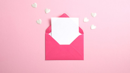 Envelope with blank white paper note inside and Valentine hearts on pink background. Romantic love letter for Valentine's or Mother's day concept.