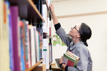 woman in the library in front of bookshelves. Concept of education