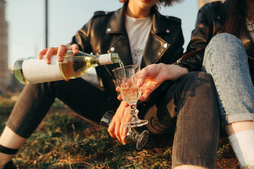 Poster de jardin Bar Background. Closeup photo of a female hand pours wine from a bottle into a glass on the street. Two stylish girlfriends drinking wine on the street while walking. Alcohol concept.