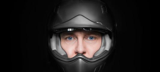Man in motorcyclist helmet on dark studio background. Closeup. Wall mural