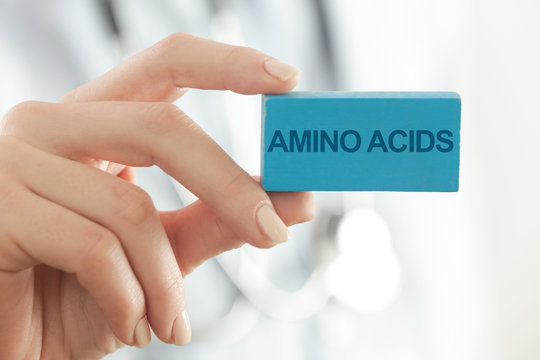 Doctor advises. Medical worker holds AMINO ACIDS signs.