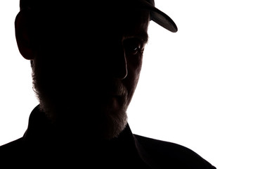 Old man in peaked cap, side view - dark close-up silhouette