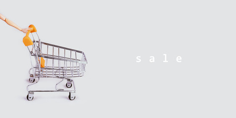 Banner with shopping cart and hand. Grocery shopping and sale concept. Black friday, online shopping and store concept. Sale discount. Background with copyspace. Creative design. Stock photography.