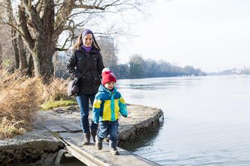 Mutter läuft mit ihrem kleinen Sohn über einen Holzsteg am Wasser, Rhein
