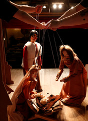 Puppeteers pose with puppets of Christmas nativity show at the Royal Toone Theatre in central Brussels