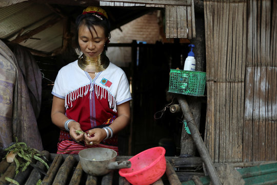 An ethnic Kayan hill tribe refugee woman, also known as long neck woman,  cooks at her hut inside their tourist attraction village near Chiang Mai