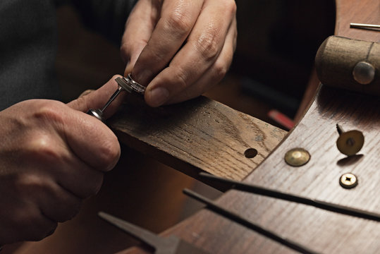 Jewelry craftsmanship. Handmade. Jeweler at work. The jeweler polishes a white gold ring with diamonds. Desktop with work tools.