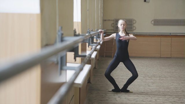 Young graceful female ballet dancer in training clothes exercising in ballet class. First position.