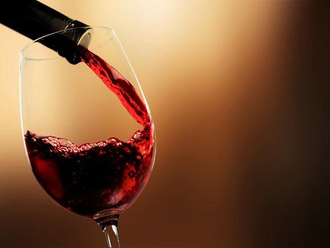 Pour red wine on blurred background