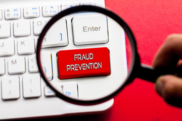 FRAUD PREVENTION word written on keyboard view with magnifier glass