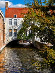 Wall Murals Bridges Brugge, Belgium. Ancient medieval old town of Bruges. Sunny day. Channel arch bridge under house with red tegular roof and tree on the banks. Summer landscape with blue sky and clouds.