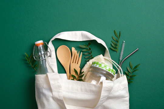 Reusable canvas shopper bag with eco friendly bamboo cutlery, metal drinking straws, glass jar and bottle. Zero waste, plastic free concept. Sustainable lifestyle