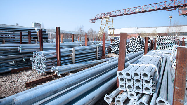 Metal warehouse outdoor of lighting poles. Storage of metal galvanized faceted pipes with flange.