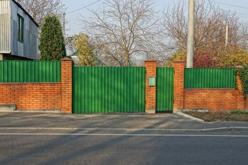 green gate and part of the fence made of metal and brown bricks on the street by a gray asphalt road