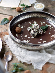 Pure chocolate truffles with almond flakes & cocoa powder on rustic wooden table with white cloth and recipe on paper. Silver and brown plate perfect for luxury food bites or rustic and delicate food
