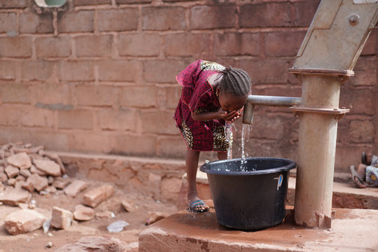 Thirsty Little African Girl Drinking Clean Fresh Water from the Village Borehole