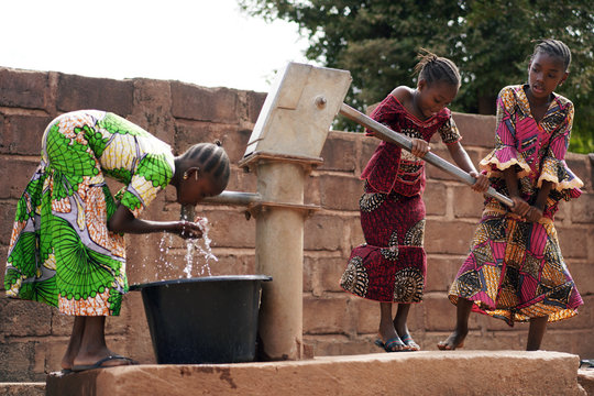 African Children At A Public Borehole Fetching Water For Their Families