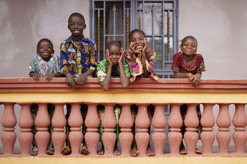 Fototapeta Group of Young African Children Linung Up On Their City Home Balcony Smiling to Bypassers obraz