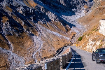 Photo sur Aluminium Sports car before a sharp bend on a mountain road Passo Dello Stelvio,autumn landscape, Dolomites, Italy