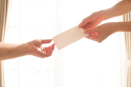 白い手紙を渡す女性の手