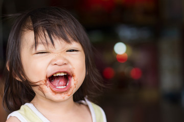 Portrait image of 1-2 yeas old baby. Happy Asian child girl eating a brown chocolate by herself. Her face messy and dirty by food.