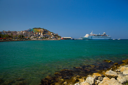 The marina in Kusadasi. The coast and port in the city, fishing boats and tourist ship. Place of holiday photos.