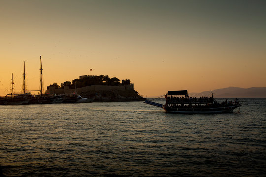 Kusadasi, Turkey - September 17, 2019: Castle on Pigeon Island in Kusadasi, Turkey. Historic Byzantine fortress on the sea.  Boat trip during sunset.