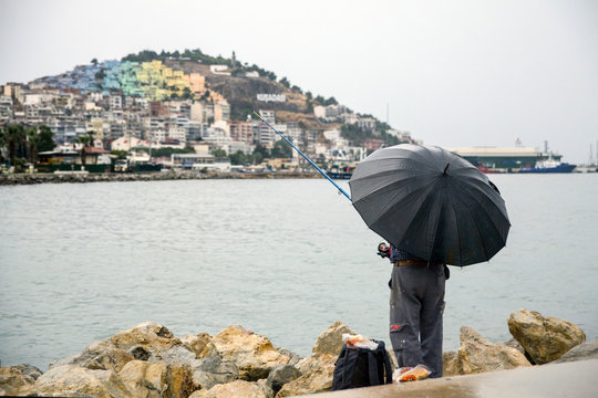 Fisherman during the rain under an umbrella catches fish.