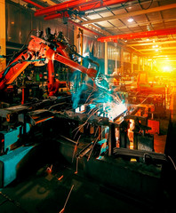 Poster de jardin Attraction parc Large factory robotic arms are spraying sparks to weld car frames