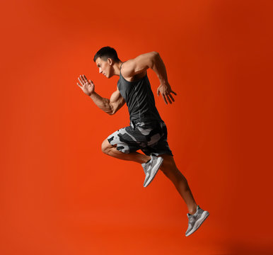 Athletic young man running on red background, side view