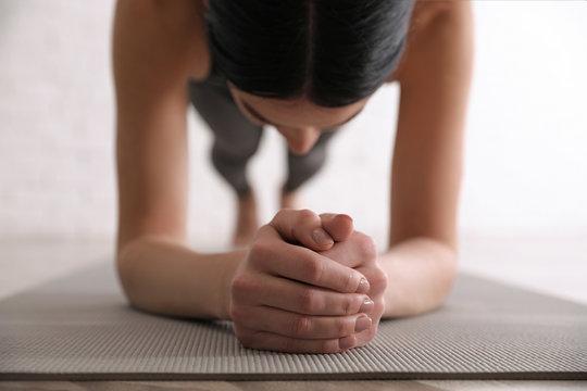Young woman practicing forearm plank asana in yoga studio, closeup. Phalankasana pose variation